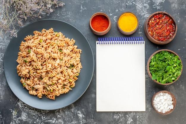 Bovenaanzicht rotini pasta op ronde plaat vork en mes zeezout kurkuma rode peper poeder in kleine kommen adjika en gehakte greens in kommen kladblok op grijze tafel
