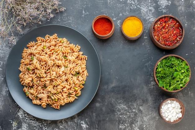 Bovenaanzicht rotini pasta op ronde plaat vork en mes zeezout kurkuma rode peper poeder in kleine kommen adjika en gehakte greens in kommen op grijze tafel vrije ruimte