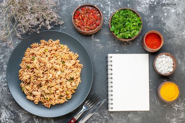 Bovenaanzicht rotini pasta op ronde plaat vork en mes zeezout kurkuma rode peper poeder in kleine kommen kladblok op grijze tafel