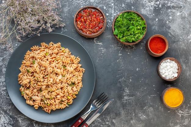 Bovenaanzicht rotini pasta op ronde plaat vork en mes zeezout kurkuma rode peper poeder in kleine kommen op grijze tafel