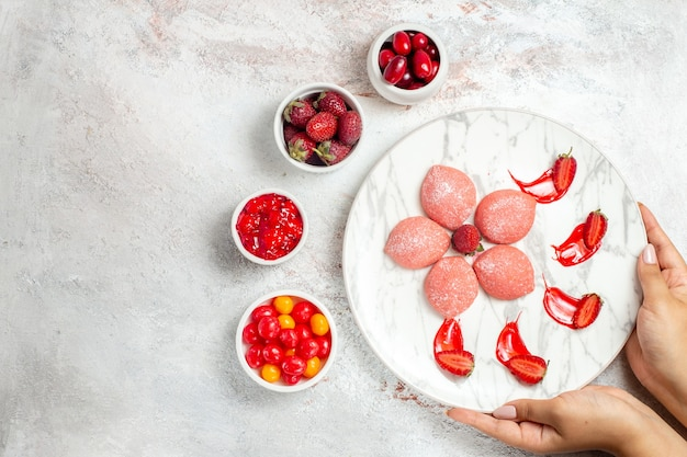 Bovenaanzicht roze aardbeientaarten kleine heerlijke snoepjes op witte achtergrond koekje suiker thee zoete koekjestaart