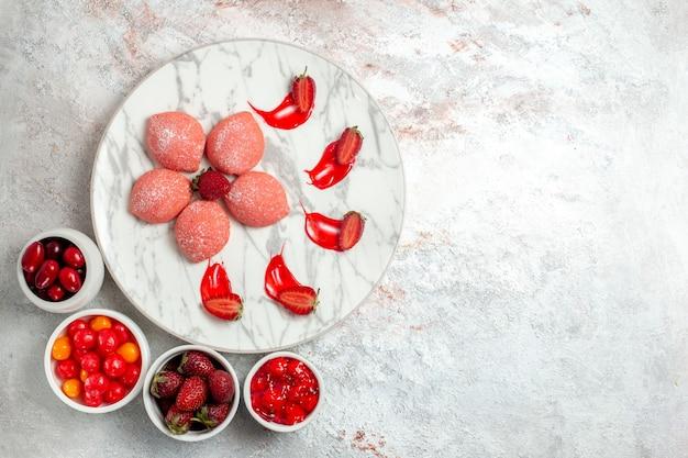 Bovenaanzicht roze aardbeientaarten kleine snoepjes in plaat op wit bureau cake suiker koekje thee koekje zoet