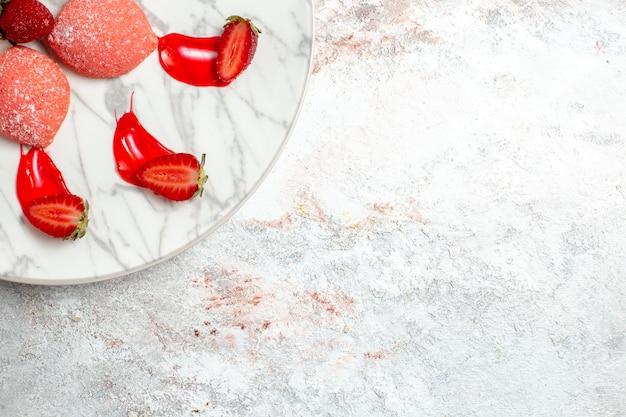 Bovenaanzicht roze aardbeientaarten kleine snoepjes in plaat op witte achtergrond cake suiker koekje thee koekje zoete vruchten