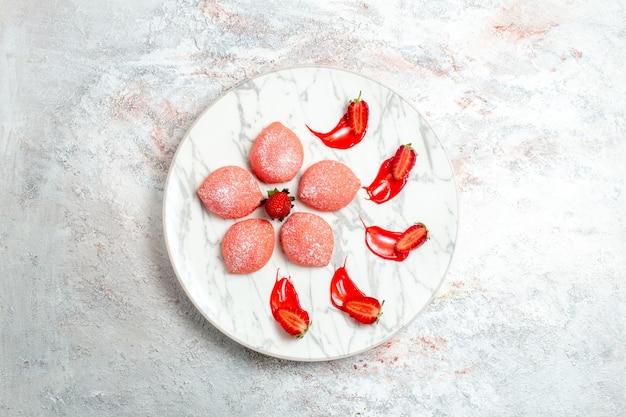 Bovenaanzicht roze aardbeientaarten kleine snoepjes op witte achtergrond cake cookie thee fruit koekje zoete suiker