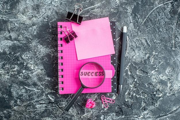 Bovenaanzicht roze blocnote met nietjes pen vergrootglas en succesnota over grijze achtergrond voorbeeldenboek school kleur student zakelijke werk baan