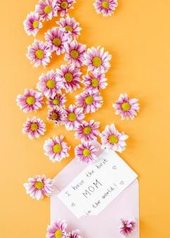 Bovenaanzicht roze bloemen en envelop