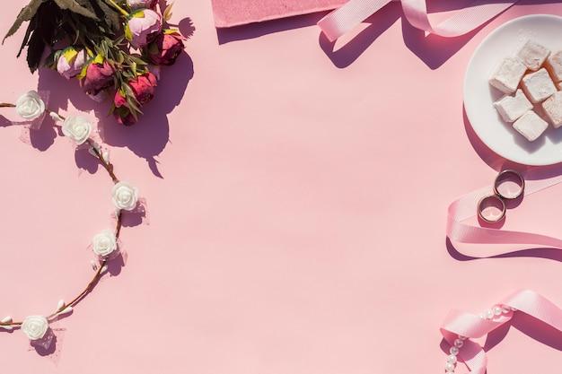 Bovenaanzicht roze bruiloft arrangement met roze achtergrond