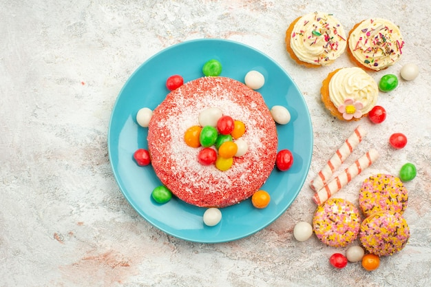 Bovenaanzicht roze cake met kleurrijke snoepjes op wit oppervlak goodie regenboog snoep dessert kleur cake