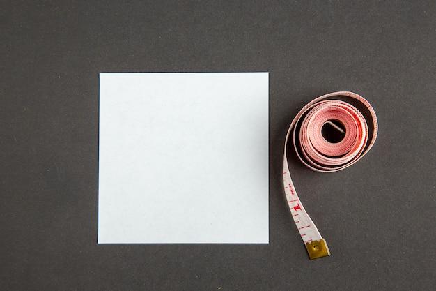Bovenaanzicht roze centimeter met papieren sticker op donkere achtergrond