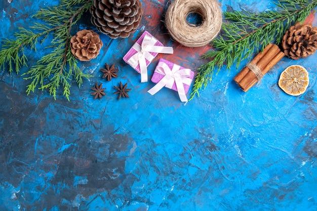 Bovenaanzicht roze kerstcadeaus pijnboomtakken kaneelstokjes anijs gedroogde citroen plakjes op blauwe oppervlakte vrije ruimte