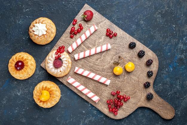 Bovenaanzicht roze kleverige snoepjes samen met bessen fruit taarten op de donkere tafel fruit bes zoete goody bonbon