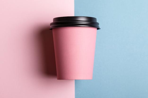 Bovenaanzicht roze papieren beker op een gekleurde achtergrond