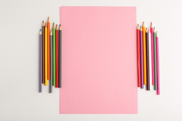 Bovenaanzicht roze papieren blanco met kleurrijke potloden op wit oppervlak