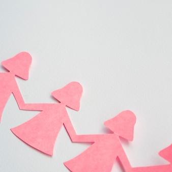 Bovenaanzicht roze papieren meisje hand in hand