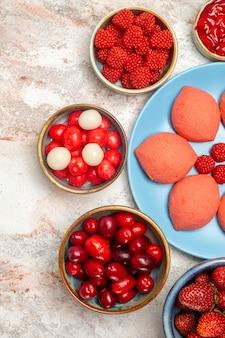 Bovenaanzicht roze peperkoek met fruit en bessen op witte bureausuiker biscuit taart zoete cake cookie