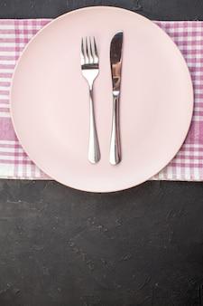 Bovenaanzicht roze plaat met mes en vork op donkere achtergrond