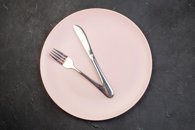 Bovenaanzicht roze plaat met mes en vork op donkere ondergrond