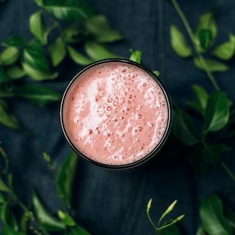 Bovenaanzicht roze smoothie naast bladeren