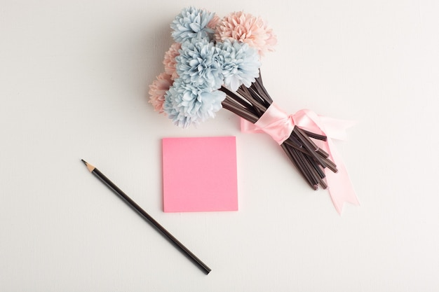 Bovenaanzicht roze sticker met potlood en bloemen op wit oppervlak