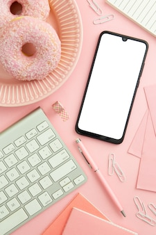 Bovenaanzicht roze werkplek samenstelling met lege telefoon