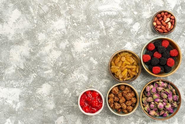 Bovenaanzicht rozijnen en noten met confitures op witte achtergrond candy cake thee confituur koekje