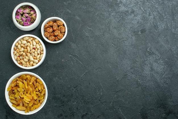 Bovenaanzicht rozijnen en noten met snoepjes op het donkere oppervlak notensnack snoep zoet