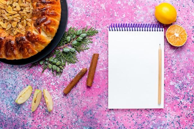 Bovenaanzicht rozijnentaart gebakken taarttaart rond gevormd met notitieblok op roze bureau