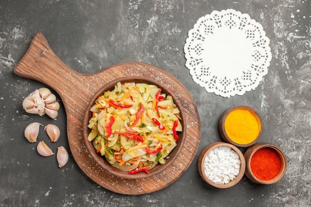 Bovenaanzicht salade groentesalade op de snijplank knoflook kant kleedje specerijen bovenaanzicht