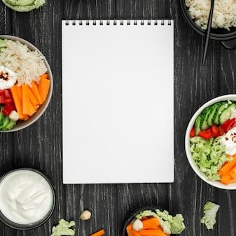 Bovenaanzicht salade met couscous en leeg notitieboekje