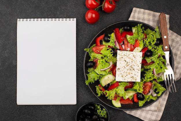 Bovenaanzicht salade met fetakaas en tomaten met leeg notitieboekje