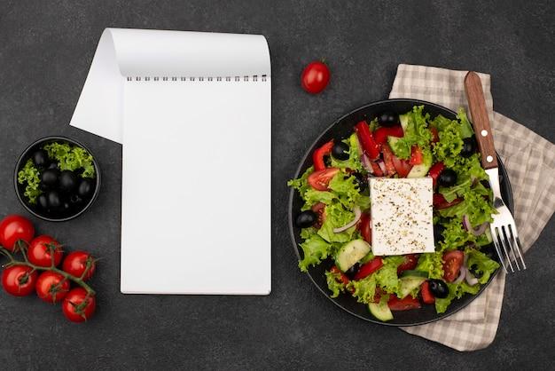 Bovenaanzicht salade met fetakaas en tomaten met lege blocnote