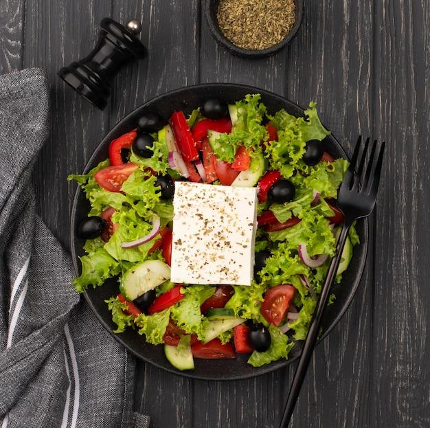 Bovenaanzicht salade met fetakaas, kruiden en vork