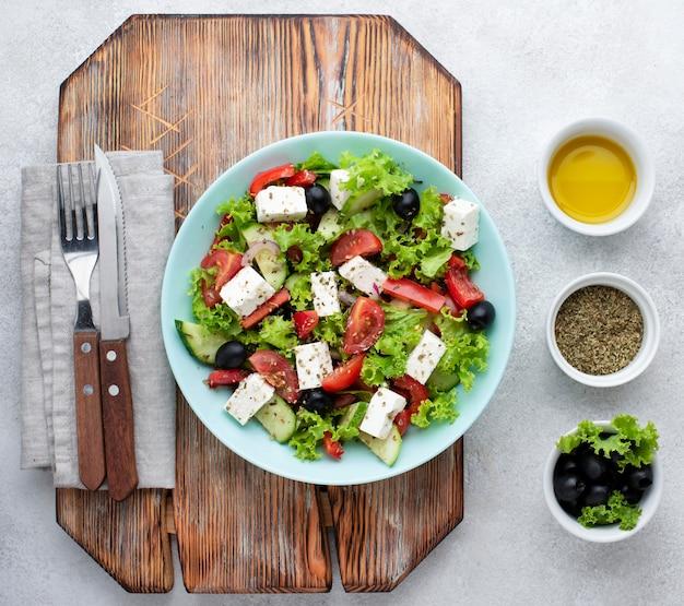 Bovenaanzicht salade met fetakaas op snijplank met olijven