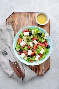 Bovenaanzicht salade met fetakaas op snijplank
