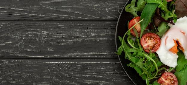 Bovenaanzicht salade met gebakken ei en kopie-ruimte