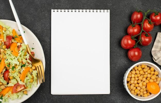 Bovenaanzicht salade met kikkererwten en tomaten met lege blocnote