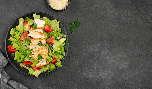 Bovenaanzicht salade met kip en sesamzaadjes met kopie-ruimte