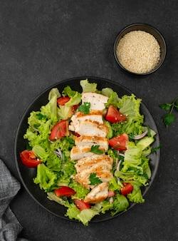 Bovenaanzicht salade met kip en sesamzaadjes