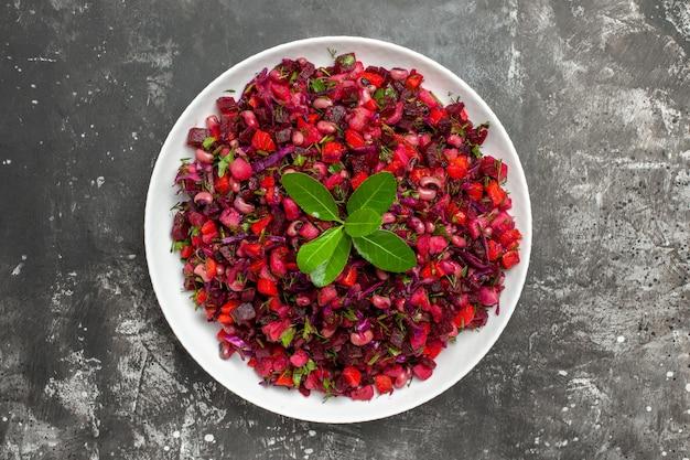 Bovenaanzicht salade met rode groente in een witte schotel op een grijze achtergrond