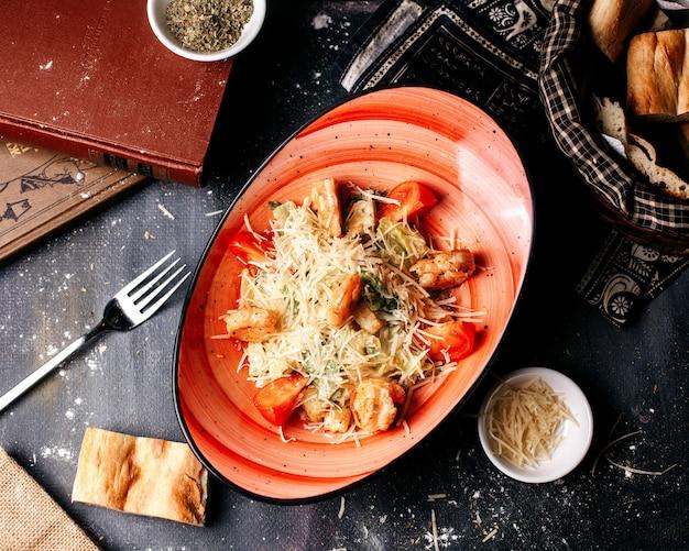 Bovenaanzicht salade met stukjes kip en verse groenten op het donkere bureau