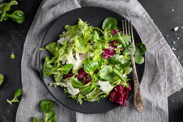 Bovenaanzicht salade met verschillende ingrediënten op een donkere plaat