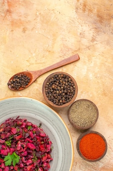 Bovenaanzicht salade op een grijze plaat met kurkuma zwarte peper en gemalen zwarte peper op houten tafel met ruimte voor tekst