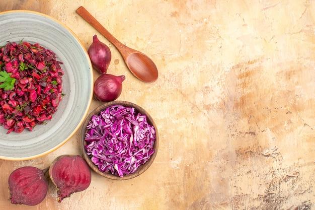 Bovenaanzicht salade op grijze plaat met groene bladeren, meng groenten met rode uien, rode bieten en gehakte kool op een houten tafel met vrije ruimte