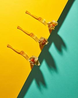 Bovenaanzicht samenstelling met gele physalis plant en vorken op diagonaal duotoon geelgroene achtergrond met zachte schaduwen. moderne stijl.