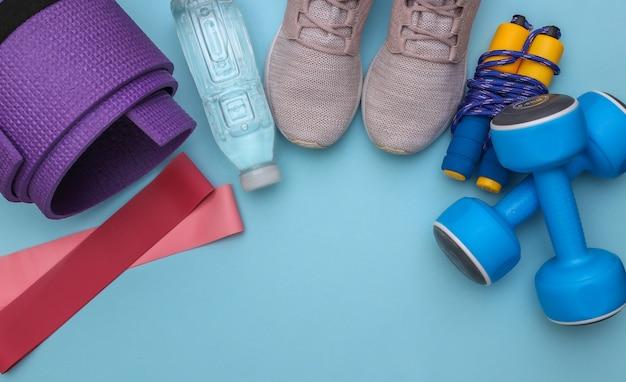 Bovenaanzicht samenstelling van fitness outfit, accessoires op blauwe achtergrond met kopieerruimte. gezonde levensstijl, sportconcept.