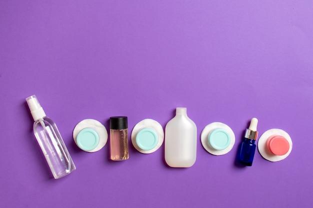Bovenaanzicht samenstelling van kleine reizende flessen en potten voor cosmetische producten op gekleurde achtergrond. gezichtsverzorgingsconcept met kopieerruimte voor uw ontwerp.