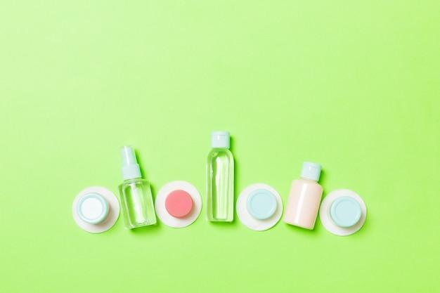 Bovenaanzicht samenstelling van kleine reizende flessen en potten voor cosmetische producten op groene achtergrond. gezichtsverzorgingsconcept met kopieerruimte voor uw ontwerp.