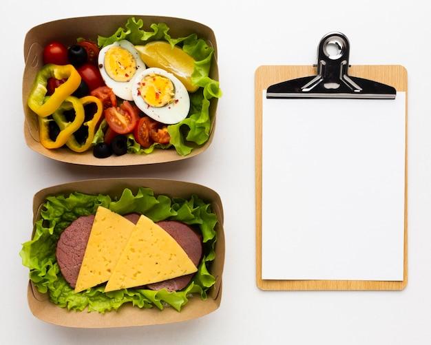 Bovenaanzicht samenstelling van verschillende maaltijden met leeg klembord