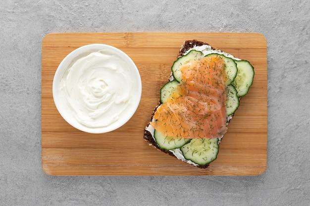Bovenaanzicht sandwich met komkommers en zalm op snijplank