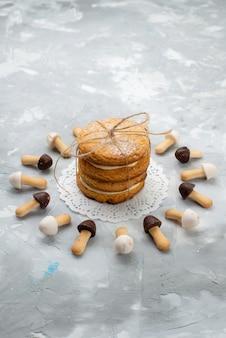 Bovenaanzicht sandwichkoekjes met crèmevulling en koekjes op de grijze zoete room van de bureausuiker